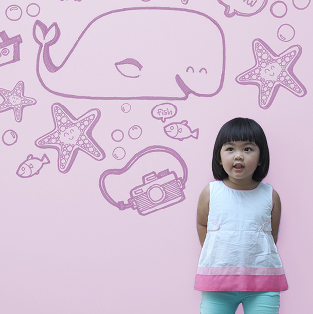 Little girl stands against a purple background with fish sketches