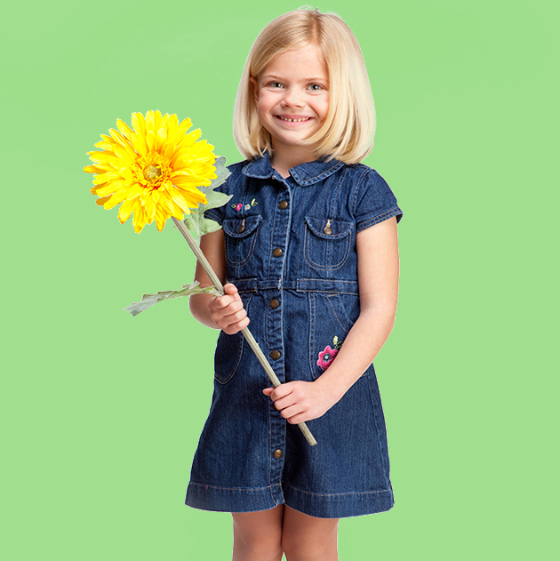Female child holding a sunflower against a green background