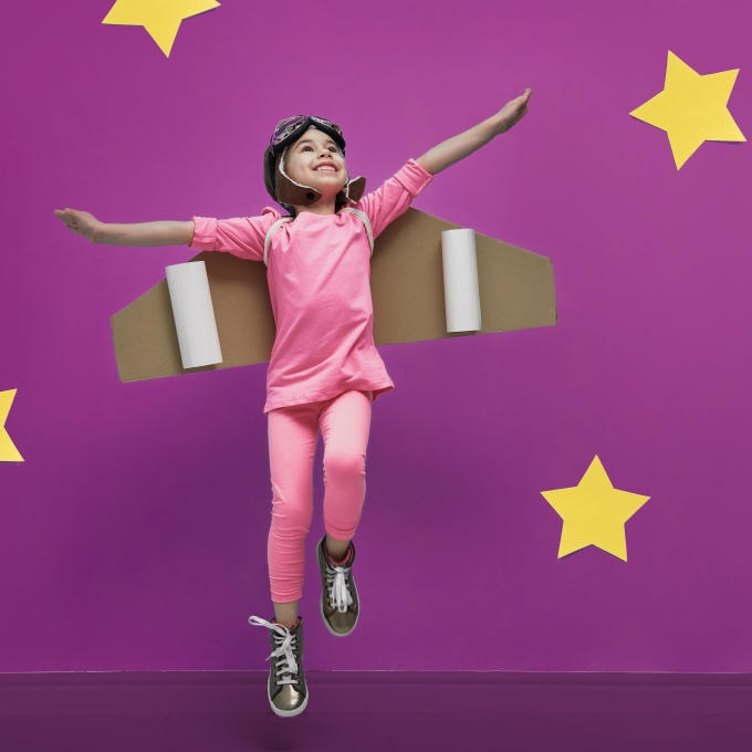Female child with cardboard wings pretends to fly